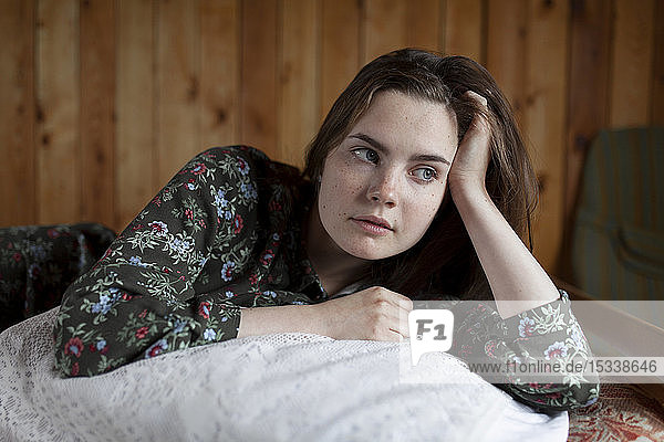 Young woman lying on cushion on bed