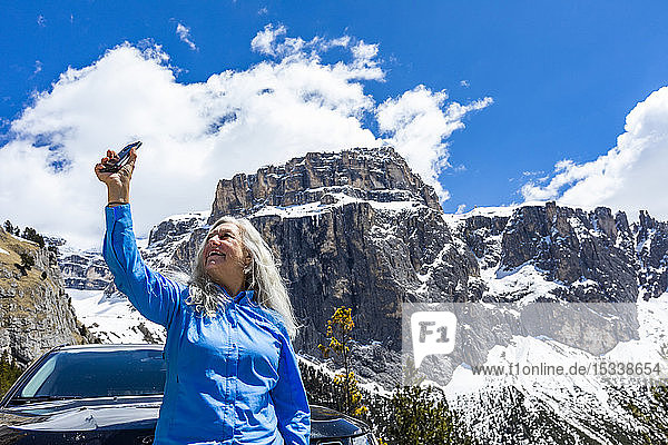 Woman taking photograph with smart phone by mountain in Dolomites  Italy