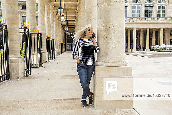Woman on phone by columns of Palais-Royal in Paris  France