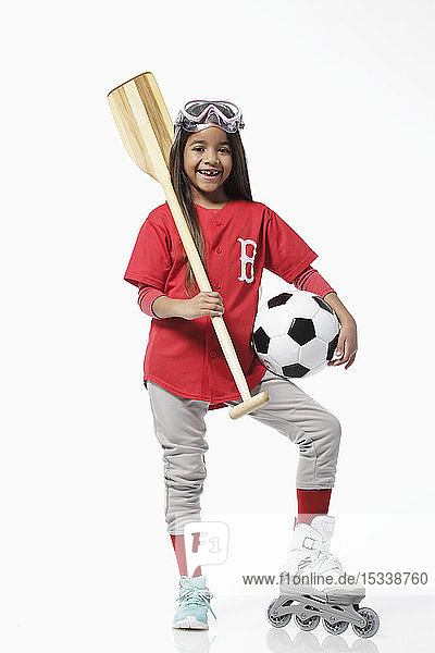 Girl dressed in baseball uniform holding sports equipment
