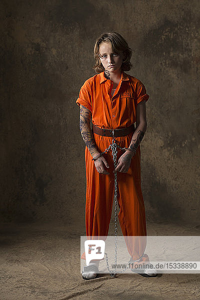 Boy in prisoner jumpsuit and handcuffs
