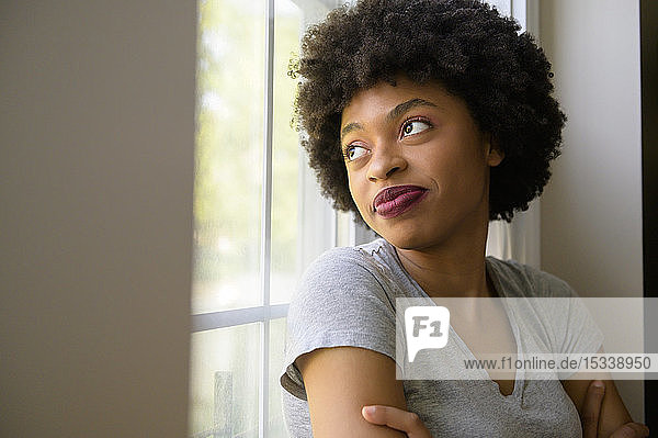 Young woman wearing lipstick by window