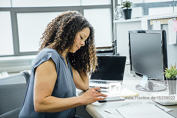 Woman using smart phone in office
