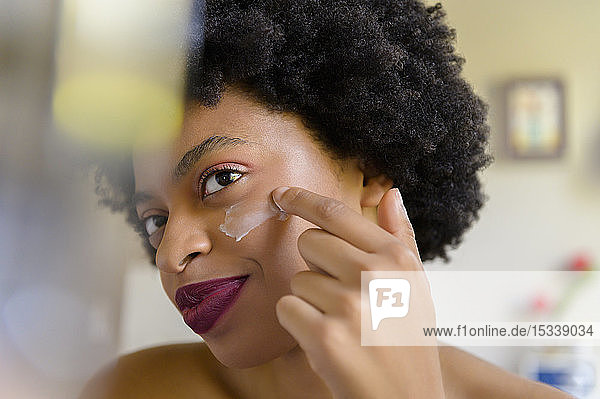 Young woman applying moisturizer to her face