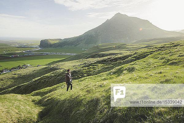 Man walking in field by mountain in Iceland