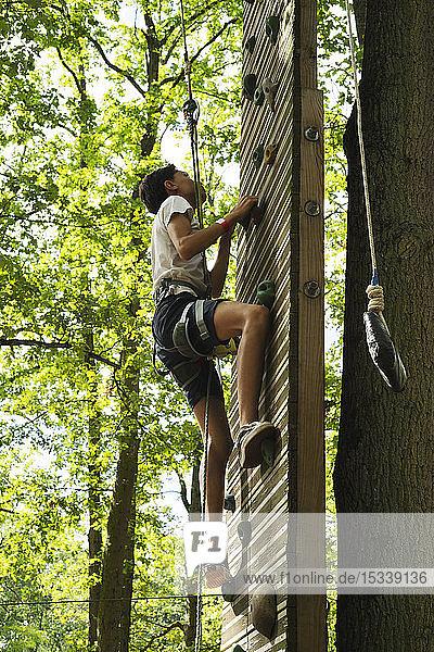 Teenage girl climbing on wall