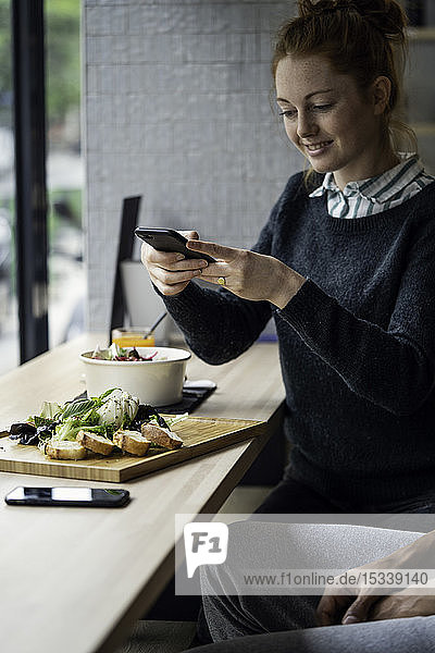 Young woman taking picture in restaurant