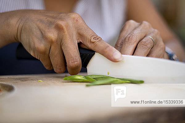 Close-up of woman cutting green beans