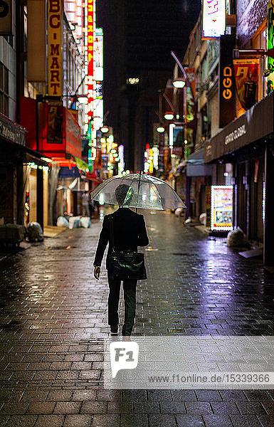 Man walking in rain with umbrella at night