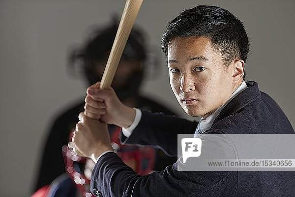 Young Japanese businessman in a suit playing baseball