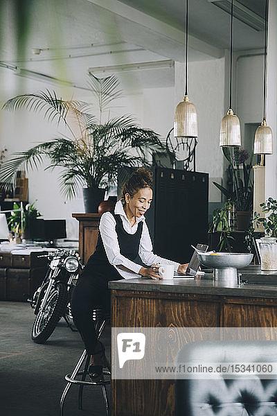 Lächelnde Geschäftsfrau sitzt auf der Kücheninsel im Kreativbüro