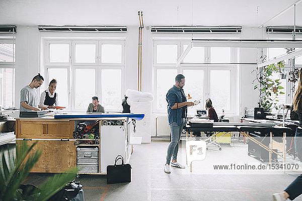 Multi-ethnische männliche und weibliche Geschäftsleute  die im Kreativbüro arbeiten