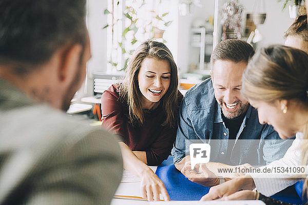 Fröhliche Unternehmer und Unternehmerinnen am Tisch während einer Sitzung im Kreativbüro