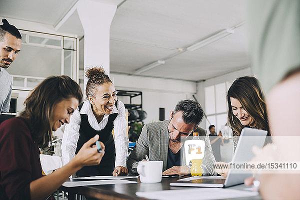 Lächelnde kreative Geschäftsleute  die im Büro am Tisch arbeiten