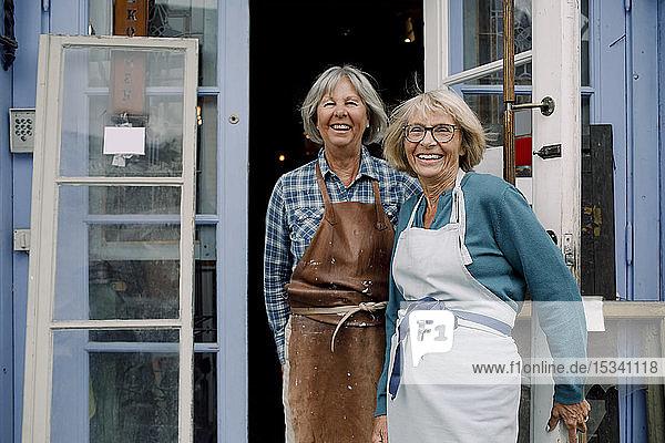 Porträt von fröhlichen älteren Besitzerinnen  die am Eingang des Geschäfts stehen