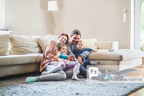 Porträt von glücklichen Eltern  die mit ihren Kindern zu Hause im Wohnzimmer sitzen