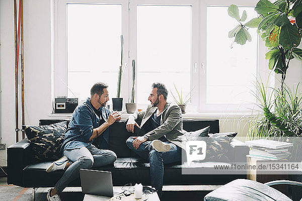 Confident male colleagues discussing while sitting on sofa in creative office