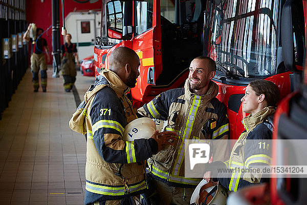 Firefighters in uniform talking while standing at fire station