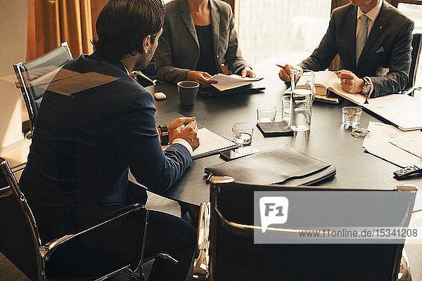 Schrägansicht von Finanzberatern  die bei einer Sitzung im Sitzungssaal diskutieren