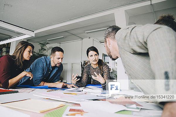 Zuversichtliche Geschäftsfrau erklärt Kollegen bei Treffen im Kreativbüro