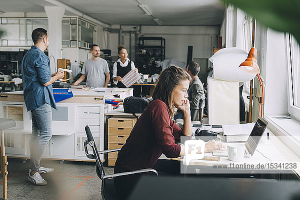 Kreative Geschäftsfrau mit Laptop am Schreibtisch  während Kollegen im Hintergrund arbeiten