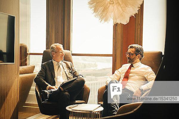 Männliche Anwälte planen  während sie in einem Anwaltsbüro am Fenster sitzen