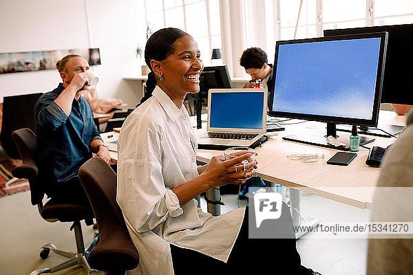 Lächelnde Geschäftsfrau trinkt etwas und schaut dabei weg  während sie mit ihrem Kollegen am Bürotisch sitzt