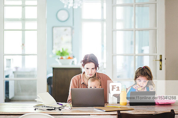 Mid adult woman working on laptop while sitting with children at home