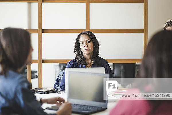 Female colleagues planning strategy while sitting in board room