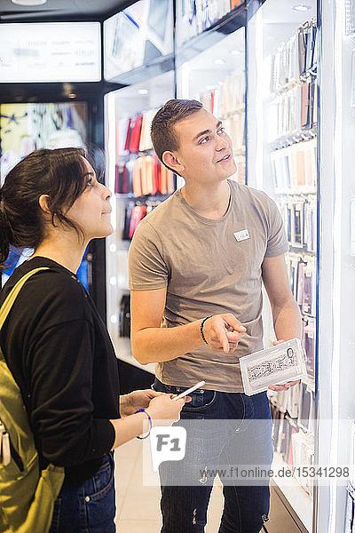Verkäufer zeigt und unterstützt junge Kundin bei der Auswahl der Telefonhülle aus beleuchtetem Regal im Laden
