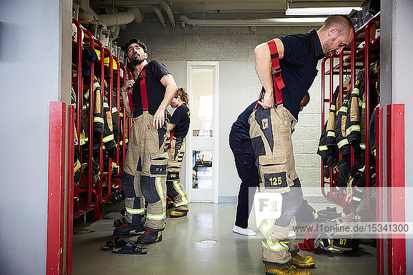 Feuerwehrleute tragen Arbeitsschutzkleidung in der Umkleidekabine der Feuerwache