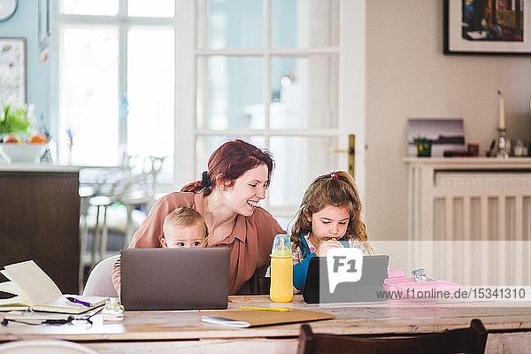 Lächelnde Frau sieht Mädchen an  die während des Essens einen Film auf einer digitalen Tablette sehen