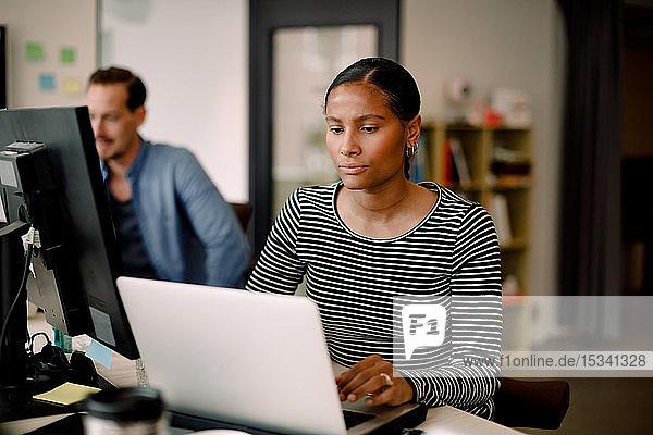 Geschäftsfrau  die nachdenkt  während sie den Laptop am Bürotisch benutzt