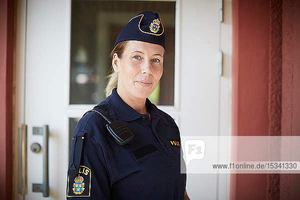 Portrait of policewoman standing outside police station
