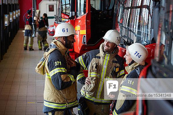 Mitarbeiter lächeln  während sie in der Feuerwache vor dem Feuerwehrauto stehen