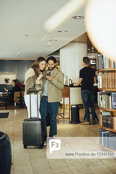 Paar mit Gepäck mit Smartphone im Restaurant stehend