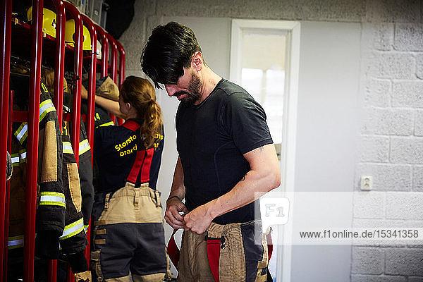 Männliche und weibliche Feuerwehrmänner und -frauen tragen Arbeitsschutzkleidung in der Umkleidekabine der Feuerwache