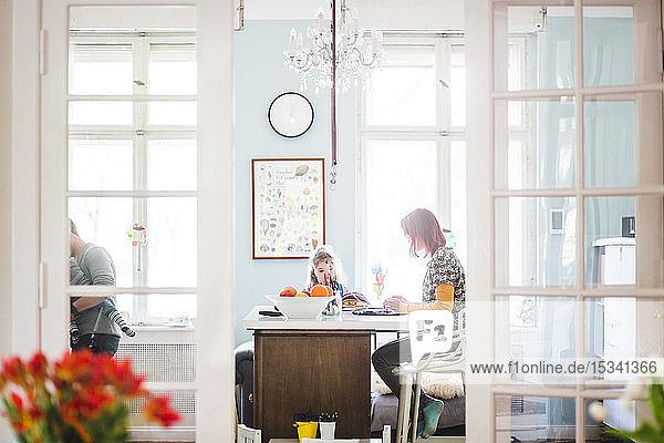 Frau arbeitet am Laptop  während sie mit einem Mädchen zu Hause in der Küche sitzt