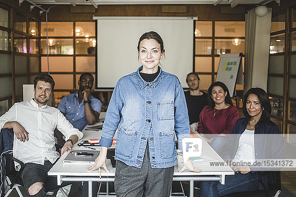 Portrait of confident businesswoman standing by coworkers sitting in board room at office
