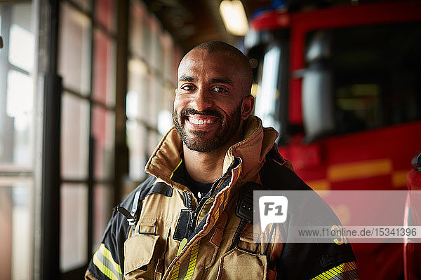 Portrait of smiling male firefighter in uniform at fire station