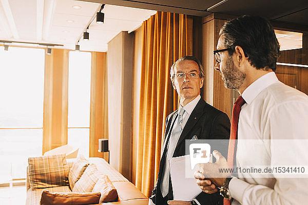 Ältere Finanzberater unterhalten sich beim Gang durch den Korridor einer Anwaltskanzlei