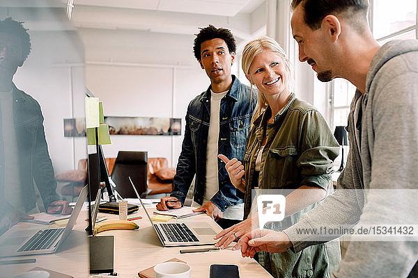 Geschäftsfrau im Gespräch mit männlichen Amtskollegen