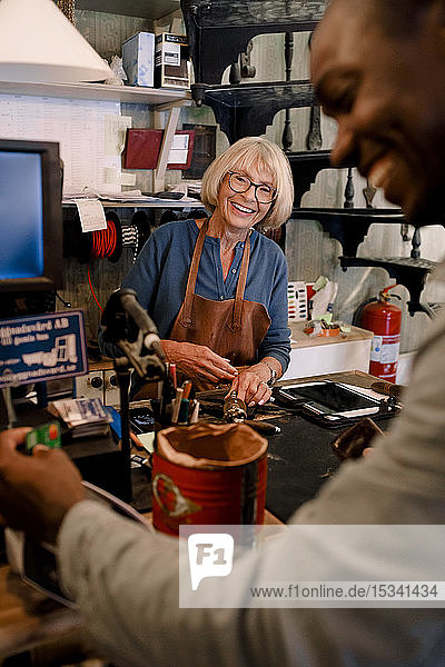 Cheerful senior saleswoman looking at male customer paying through credit card in hardware store