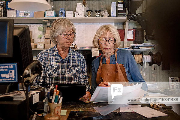 Confident senior female owners discussing over documents at checkout in hardware store