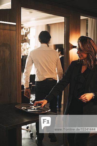 Weibliche Beraterin hält das Smartphone auf dem Tablett vor dem Sitzungssaal mit der Kollegin im Hintergrund