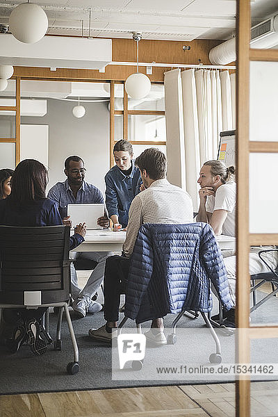 Male and female coworkers brainstorming in meeting at creative office