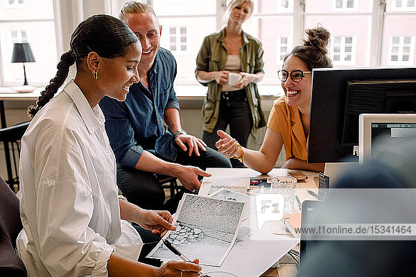 Business people discussing over photographs while sitting at desk in office