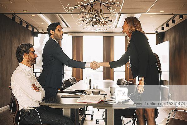 Männliche und weibliche Anwälte schütteln sich im Sitzungssaal im Büro die Hand