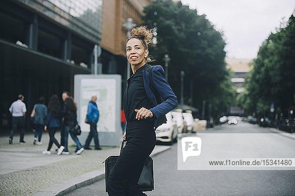 Seitenansicht einer Geschäftsfrau  die beim Überqueren einer Straße in der Stadt wegschaut
