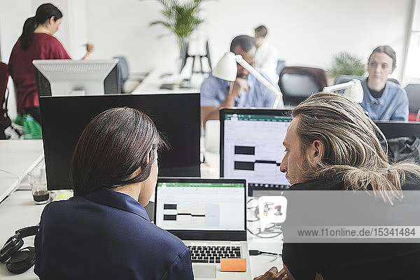 Male and female professionals discussing over laptop on desk in creative office